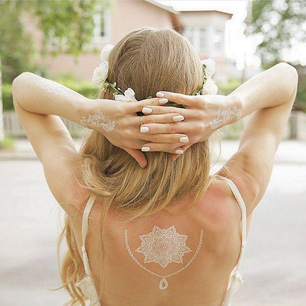 tatuagem temporária de henna branca que imita renda nas costas e mãos